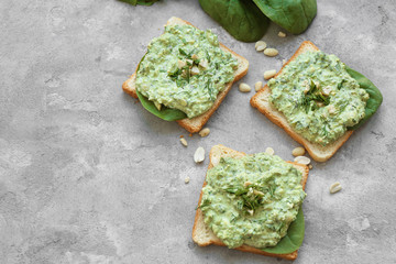 Toasts with tasty spinach sauce on table