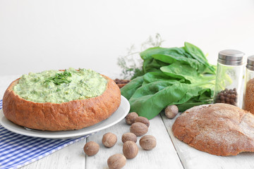 Bread loaf filled with tasty spinach sauce on table