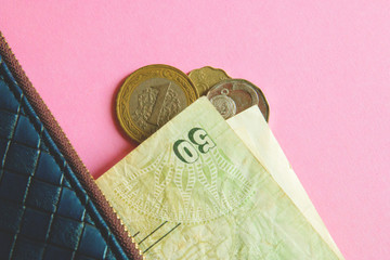 Coins and banknotes of different countries in blue wallet on pink background