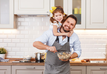 happy family in kitchen. Father and child daughter knead dough and bake biscuits