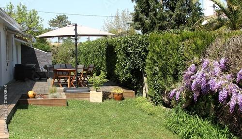 terrasse en bois exotique et salon de jardin près d\'une haie de ...