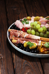 Italian antipasti wine snacks set. Cheese variety, Mediterranean olives, pickles, Prosciutto di Parma, salami and wine in glasses over black grunge background.
