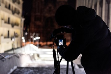 A man is photographing a building in winter