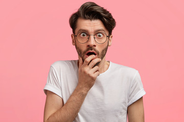 Candid shot of handsome young male journalist in eyewear, looks with astonished expression, forgets questions for interview, wears casual t shirt, poses against pink background. Emotions concept