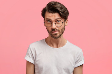 Horizontal portrait of serious unshaven male manager looks with thoughtful hesitant expression, curves lips, tries to find solution in mind, wears casual white t shirt, isolated over pink background