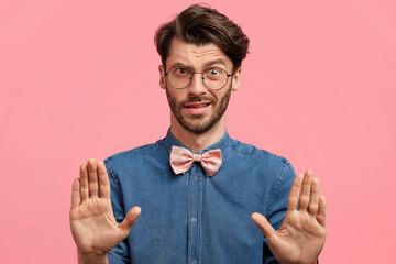 Elegant male youngster dressed in denim shirt with pink bowtie, gestures with discontent expression in studio, demonstrates his refusal and disagreement. Stylish male shows stop sign indoor, says no