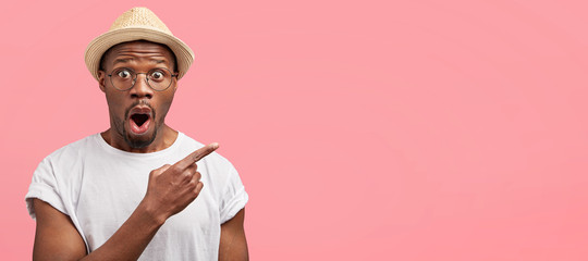 Horizontal studio shot of greatly surprised mixed race male wears stylish hat and casual white t shirt, advertises something with amazed expression, feels excited, blank copy space for your text Wall mural