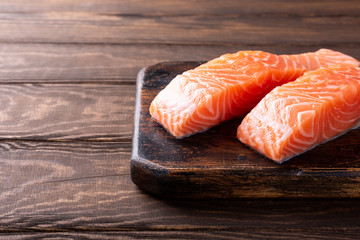 Fresh raw salmon fillet. Old wooden background. Copy space. Selective focus.