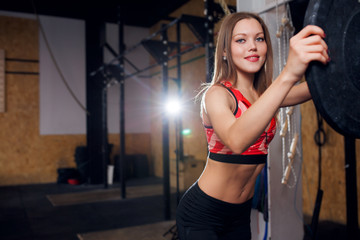 Image of smiling sportswoman with barbell