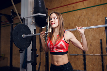 Picture of sporty woman with barbell in arms