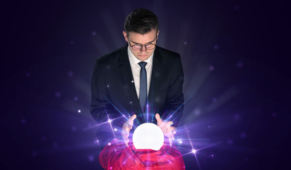 Young businessman sitting with crystal ball in action