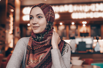 beautiful young Arab girl with headscarf in hijab, sitting in cozy cafe and smiling