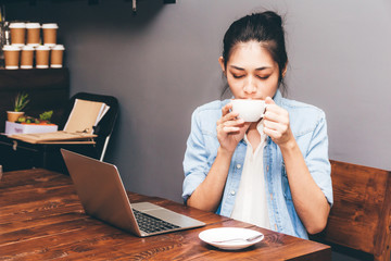 Woman drinking coffee and work on laptop computer at coffee cafe