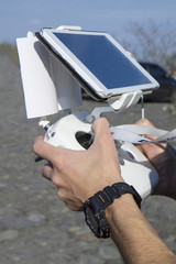 Man hands holding remote controller using tablet for drones flying.