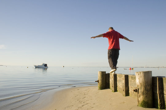 A man walking along a small wooden barrier, balancing in a beautiful and calm environment.