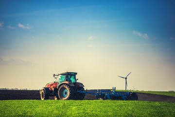 Wall Mural - Farmer with tractor seeding crops at field