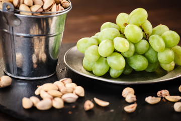 Pistachios and plums on wooden table