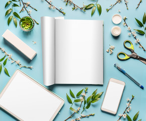 Modern desktop workplace flat lay with mock up open magazine , tablet computer and smart phone, cosmetic products spring blossom and green leaves on blue background, top view.