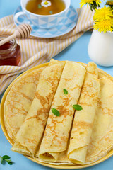 Stack of thin pancakes crepes for breakfast with honey and tea