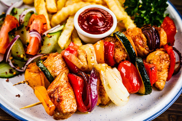 Kebabs - grilled meat with french fries and vegetables on wooden background