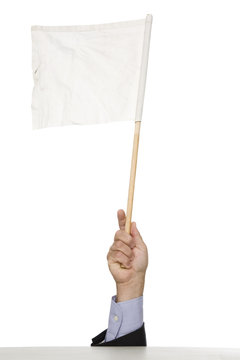 A man raises a white flag above hiding spot.