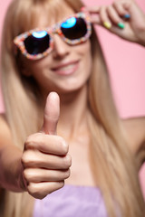 Female portrait with shallow depth of focus. Young blonde smiling  woman with fun candy glasses and thumb up