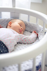 Newborn baby at home. New born child in wooden co-sleeper crib. Infant sleeping in bedside bassinet. Little girl taking a nap.