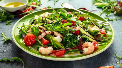 Fresh Avocado, shrimps salad with lettuce green mix, cherry tomatoes, herbs and olive oil, lemon dressing. healthy food