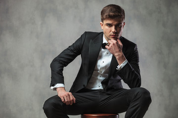pensive businessman in black tuxedo sitting on chair
