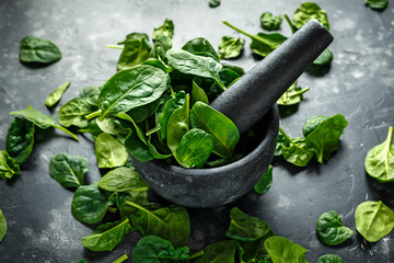 Fresh organic spinach leaves in marble pestle ready for pesto making