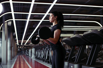 athletic woman pumping up muscules with barbell