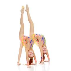 Two girls gymnast doing a bridge.