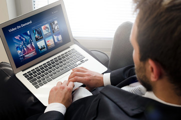 Man using laptop for watching movie on VOD service.