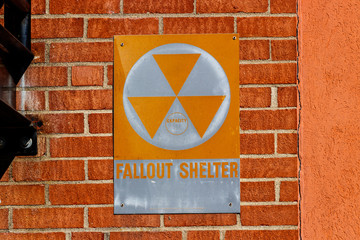 "Orange ""Fallout Shelter"" sign on a brick wall. With North Korea performing nuclear missile tests, Fallout Shelters may become more popular I"