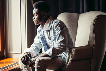 african young Man sitting in armchair at cafe and looking at window