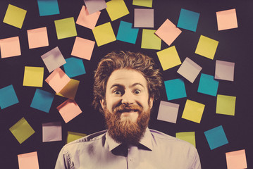 Portrait of a cheerful bearded man against a black background. Toned image.