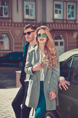 Trendy fashionable couple standing near the car