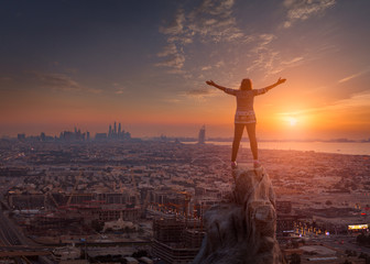 Women standing on the cliff towards the cityscape and setting sun