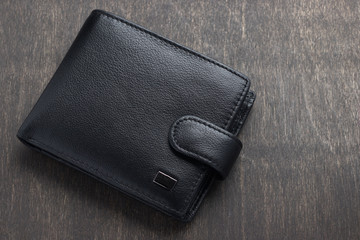 black leather wallet on a wooden background