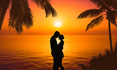 silhouette of a couple on tropical beach at sunset