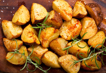roasted potatoes with rosemary on wooden board