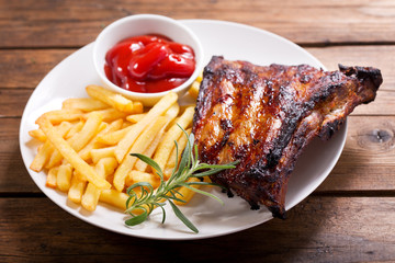 plate of grilled pork ribs with french fries