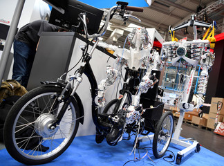 "Parts of a humanoid robot are seen on a bike during a media tour at the world's biggest industrial fair, ""Hannover Fair"", in Hanover"
