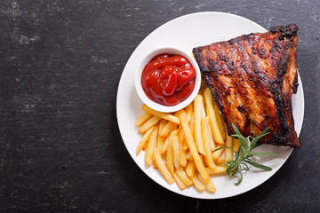 plate of grilled pork ribs with french fries, top view