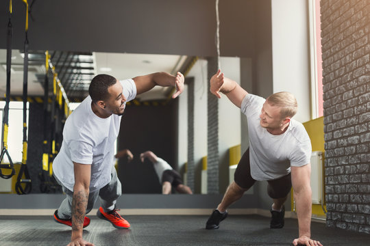 Two happy men fitness workout together at gym