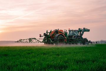 Pflanzenschutz in der Landwirtschaft, Landwirt spritzt sein Getreide beim Sonnenuntergang
