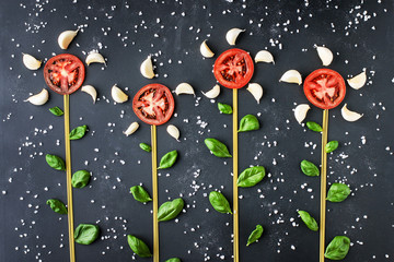Growing flowers made from pasta, tomato and basil on a dark background