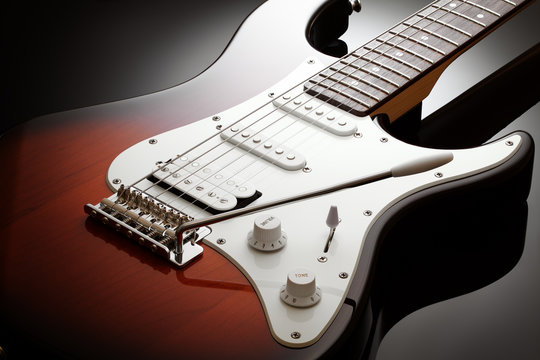Close up on the body of elegant electric guitar with sunburst finish, black glossy background
