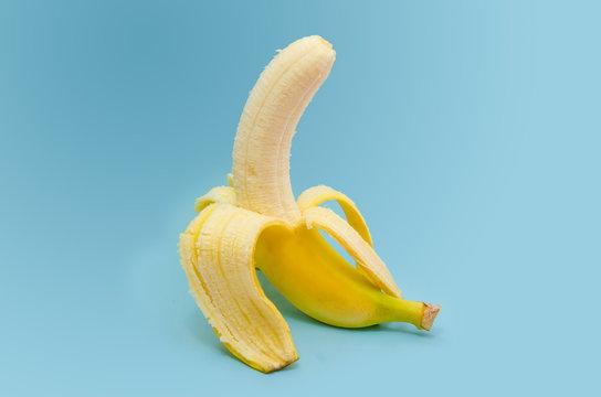 Fresh peeled banana on blue background