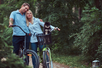 An attractive couple of a blonde female and man dressed in casual clothes on a bicycle ride with their cute little spitz in a bicycle basket.